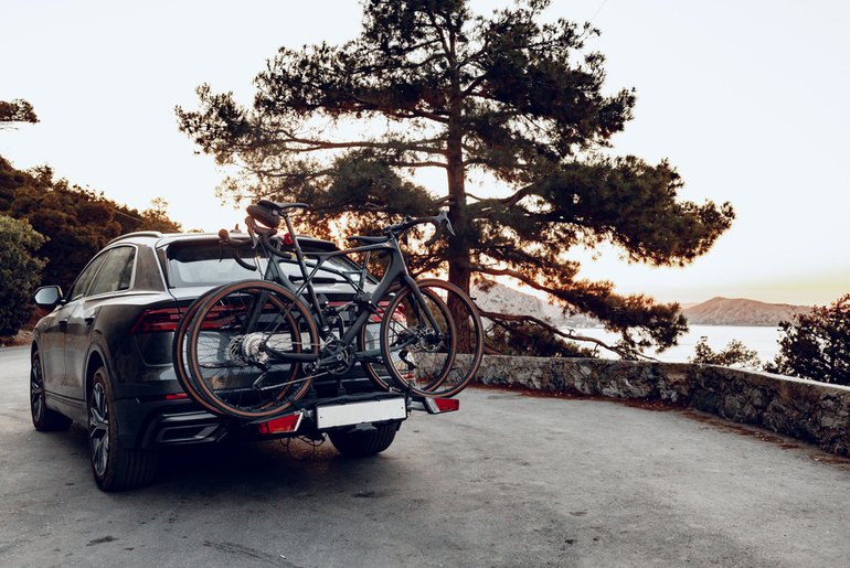SUV with bicyles on the back on a coastal road