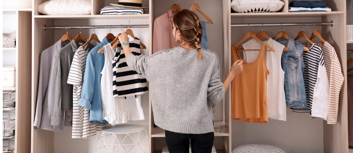 woman organizing clothes in a wardrobe