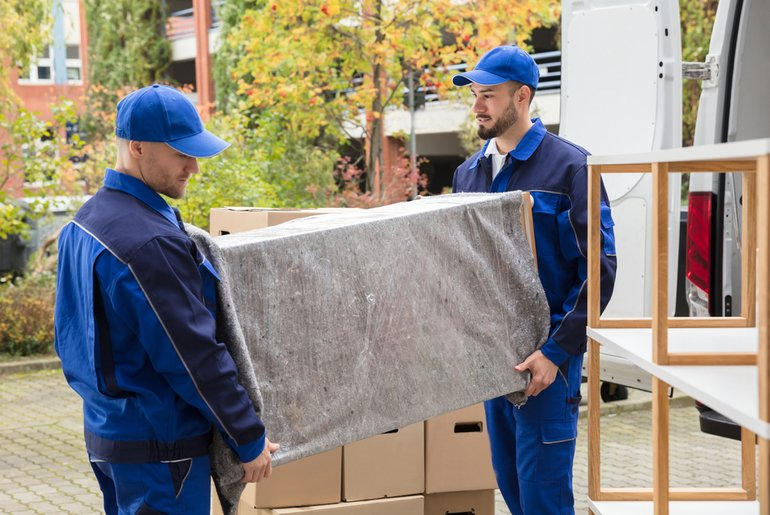 movers moving wrapped furniture