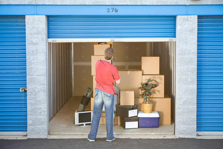 Man opening self storage unit with boxes