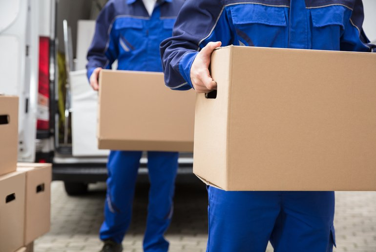 Removal men carrying boxes from van