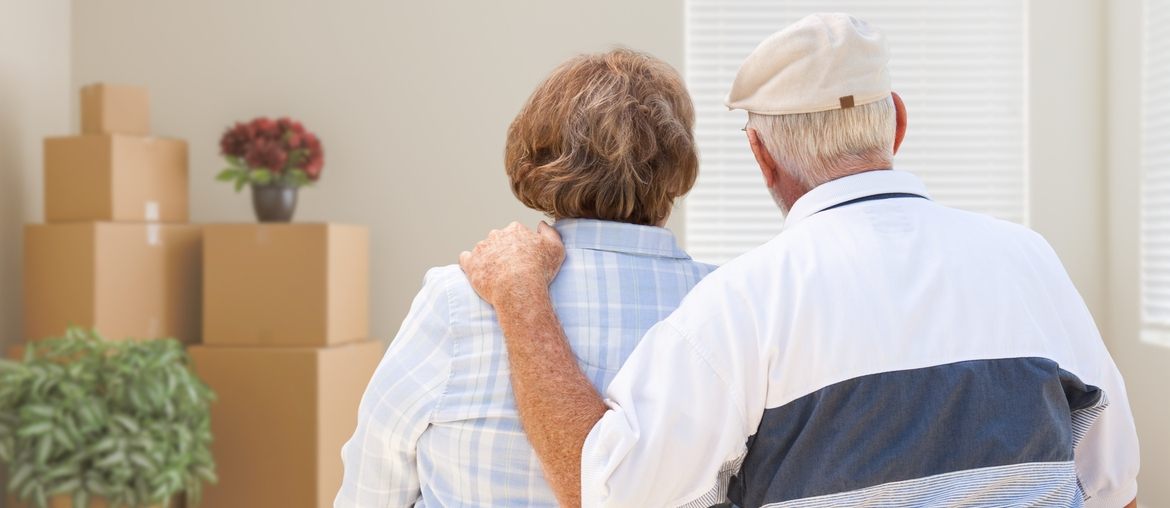 Senior couple with moving boxes in room